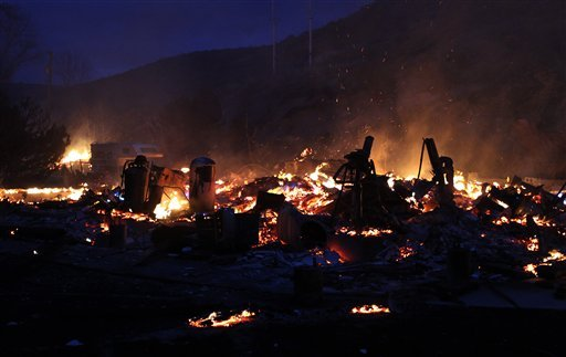 The ruins of a home in Pleasant Valley, south of Reno, Nev. smolders as firefighters battle a wind-driven brush fire on Thursday, Jan. 19, 2012. (AP Photo/Cathleen Allison)