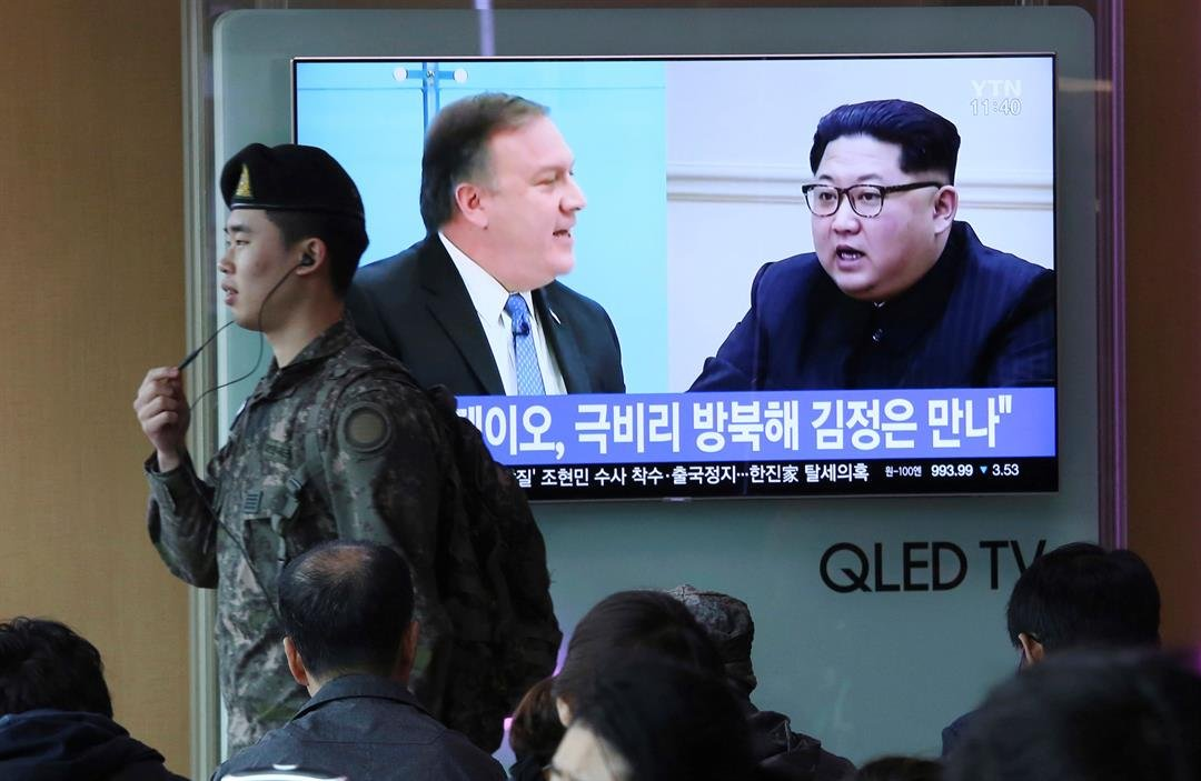 A South Korean army soldier passes by a TV screen showing file footage of CIA Director Mike Pompeo, left, and North Korean leader Kim Jong Un during a news program at the Seoul Railway Station in Seoul, South Korea (AP Photo/Ahn Young-joon)