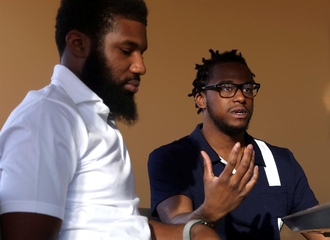 Rashon Nelson, left, listens as and Donte Robinson, right, addresses a reporter's question during an interview with The Associated Press in Philadelphia. (AP Photo/Jacqueline Larma)