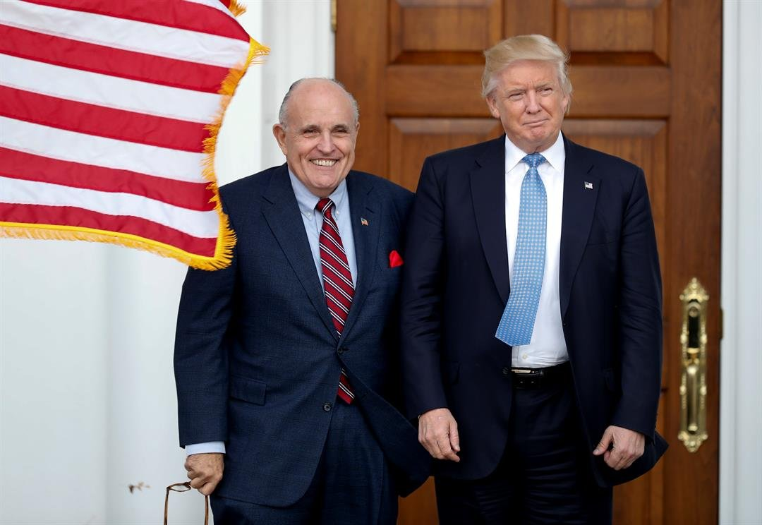 FILE - President-elect Donald Trump, right, and former New York Mayor Rudy Giuliani pose for photographs as Giuliani arrives at the Trump National Golf Club Bedminster clubhouse, Sunday, Nov. 20, 2016, in Bedminster, N.J.. (AP Photo/Carolyn Kaster)