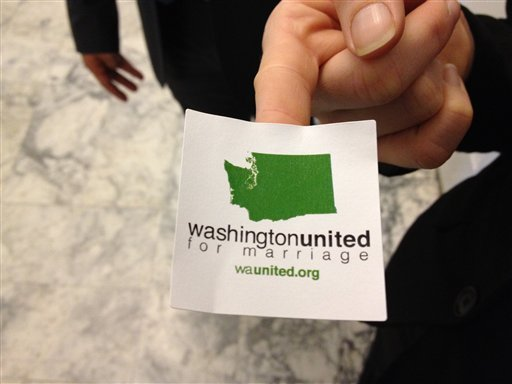 A supporter of gay marriage hands out stickers outside an overflow room for a Senate committee hearing on proposed legislation that would legalize same-sex marriage, Monday, Jan. 23, 2012, at the Capitol in Olympia, Wash. (AP Photo/Ted S. Warren)