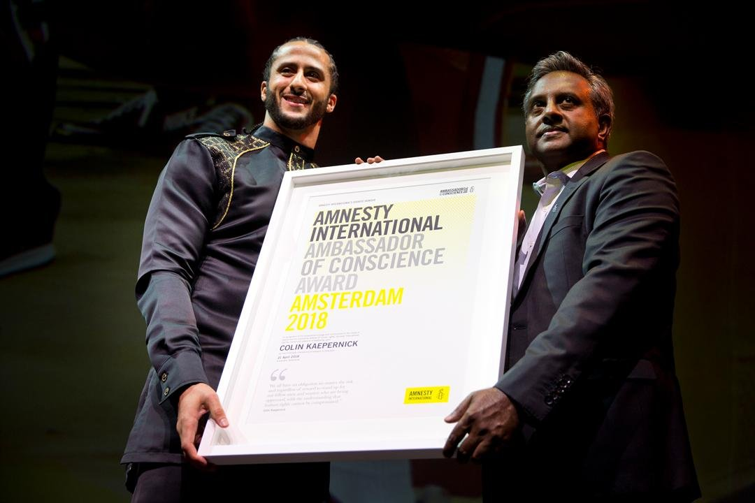 Former NFL quarterback and social justice activist Colin Kaepernick receives the Amnesty International Ambassador of Conscience Award for 2018 from Amnesty International Secretary General Salil Shetty. (AP Photo/Peter Dejong)