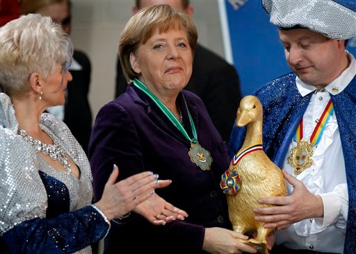 German Chancellor Angela Merkel, center, reacts after she received a 'Golden Goose' by Prince Frank I., right, and Princess Petra I. during a reception of carnival clubs from all over Germany at the chancellery in Berlin, Germany, Tuesday, Jan. 24, 2012.