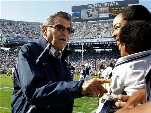 FILE - In this Oct. 8, 2011 file photo, Penn State head football coach Joe Paterno, left, talks with a football recruits' family on the sidelines during warm-ups before an NCAA college football game against Iowa, in State College, Pa.