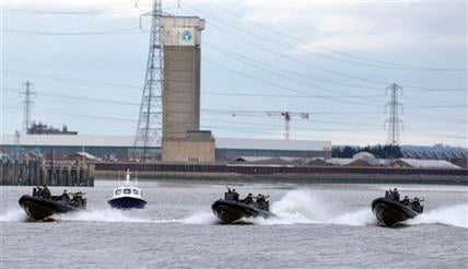 Police and Royal Marines boats perform during a combined security exercise on the River Thames in London Jan. 19, 2012. The security exercise was performed in preparation for the London 2012 Olympic games. (AP Photo/Kirsty Wigglesworth)