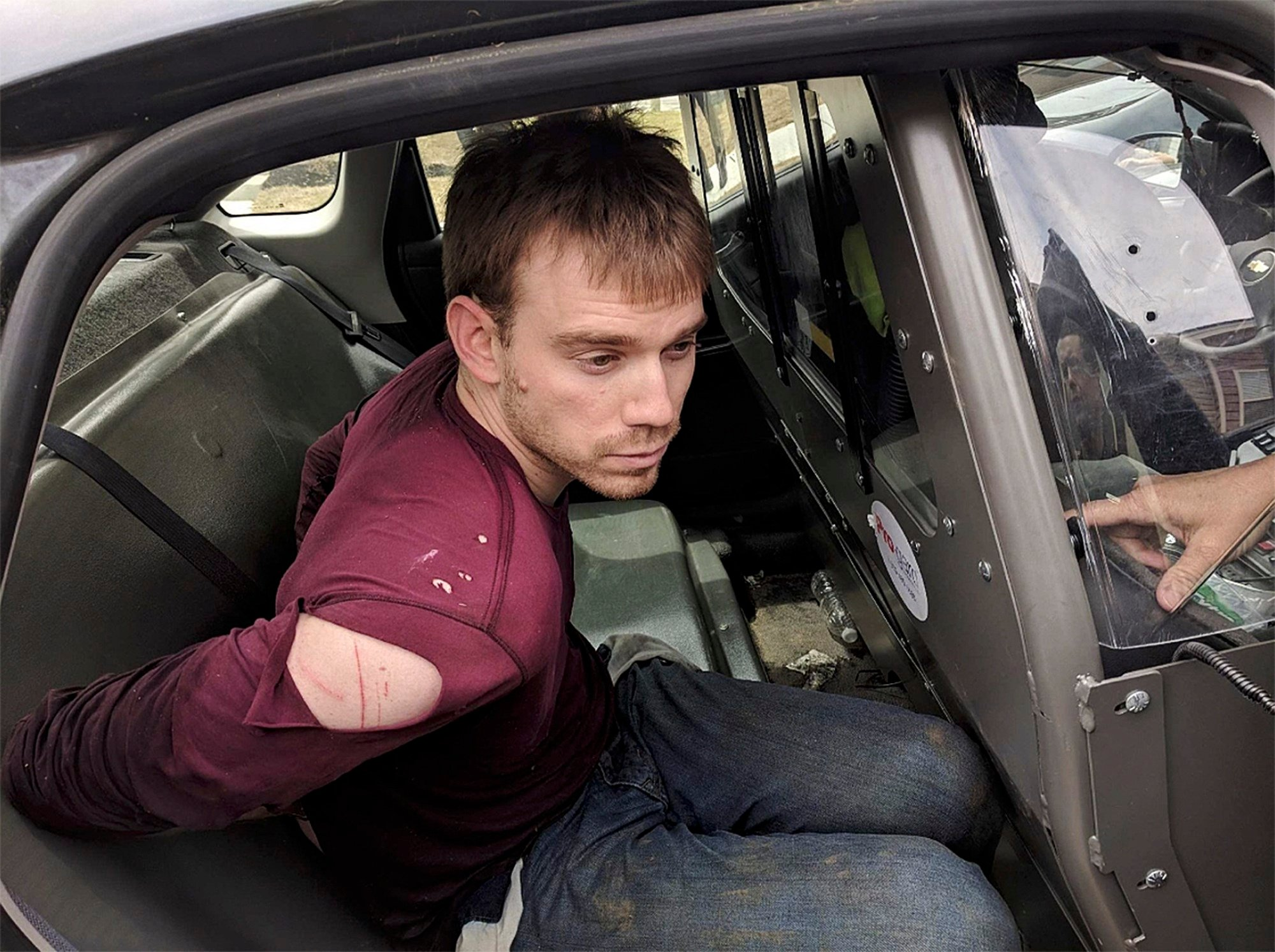 Travis Reinking sits in a police car after being arrested in Nashville, Tenn., on Monday, April 23, 2018. Police said Reinking opened fire at a Waffle House early Sunday, killing at least four people. (Metro Nashville Police Department via AP)