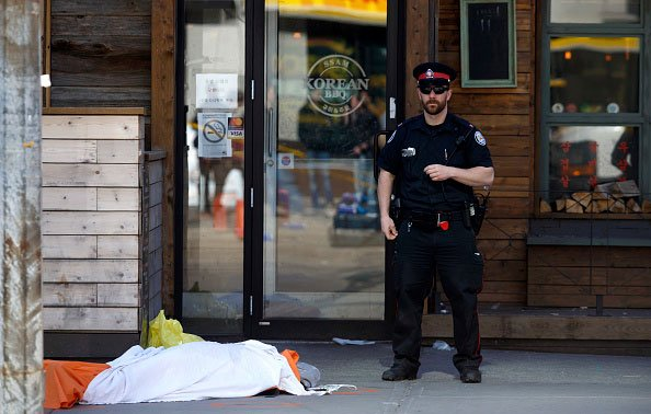 A tarp covers an unidentiified body on Yonge St. at Finch Ave. after a van plowed into pedestrians on April 23, 2018 in Toronto, Ontario, Canada. (Photo by Cole Burston/Getty Images)