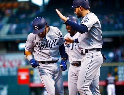 San Diego Padres' Carlos Asuaje, left, is congratulated by Eric Hosmer, front right, and Jose Pirela while crossing home plate after hitting a three-run home run off Colorado Rockies starting pitcher Chad Bettis in the first inning of a baseball game Mond