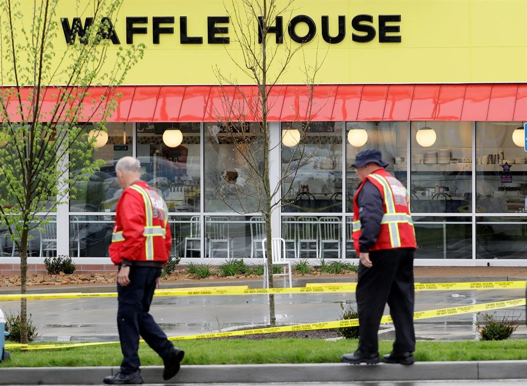 Emergency workers walk outside a Waffle House restaurant Sunday, April 22, 2018, in Nashville, Tenn. At least four people died after a gunman opened fire at the restaurant early Sunday.(AP Photo/Mark Humphrey)