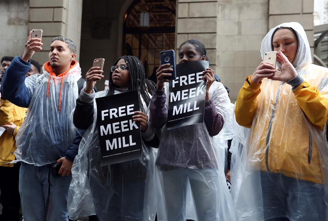 Protesters uses their phones and listen to a speaker in front of a courthouse during a hearing for rapper Meek Mill, Monday April 16, 2018 in Philadelphia. (AP Photo/Jacqueline Larma)