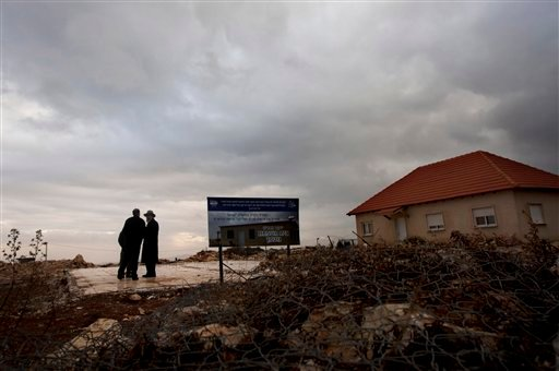In this photo taken Monday, Jan. 23, 2012 Jewish settlers walk near the remaining foundations of a demolished house, with a sign wishing its rebuilding, in the unauthorized West Bank Jewish settlement of Migron.
