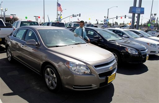 FILE - In this Aug. 30, 2011 file photo, 2011 Chevrolet Malibus are lined up at a car dealership in San Jose, Calif. (AP Photo/Paul Sakuma, File)