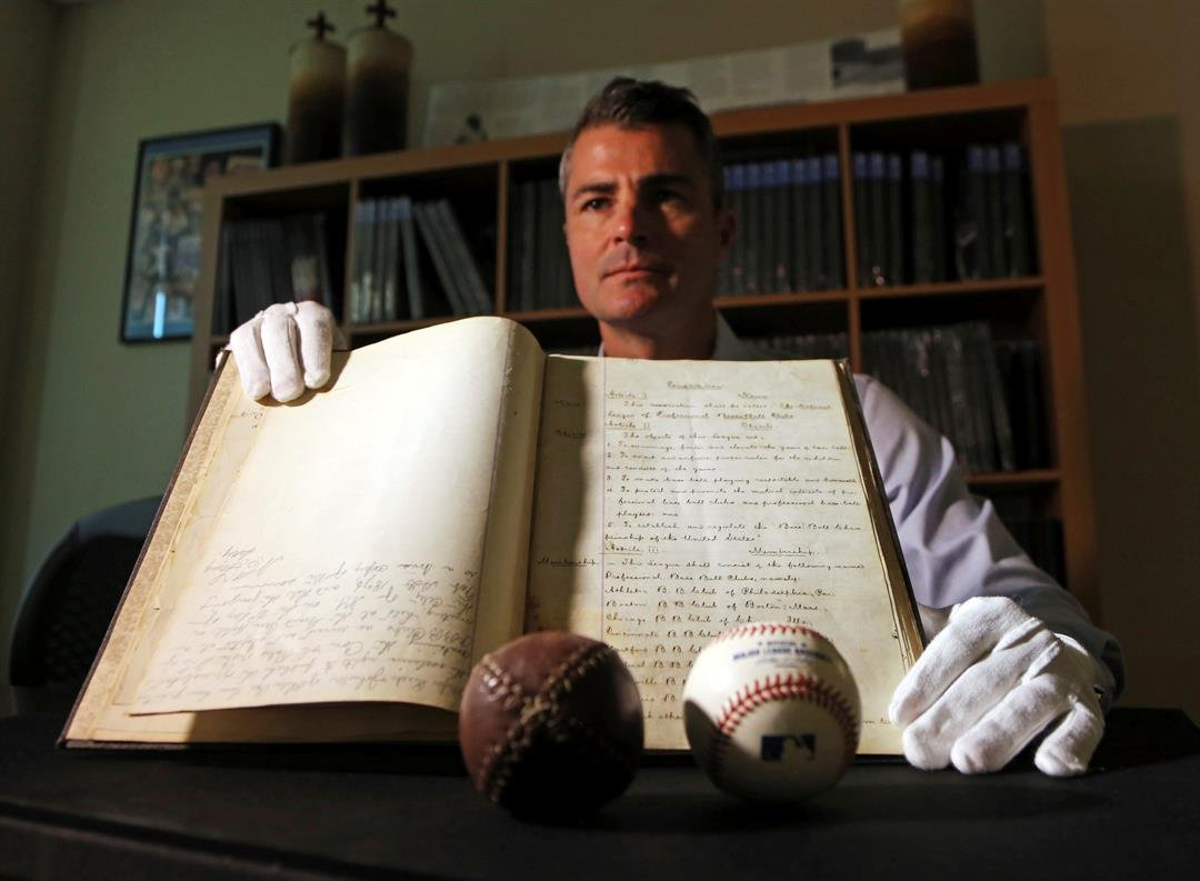 This May 18, 2017, photo shows Dan Imler, vice president of SCP Auctions, with the bound volume of the 1876 constitution that founded the National League of Professional Base Ball and the modern business of big league sports. (AP Photo/Reed Saxon)