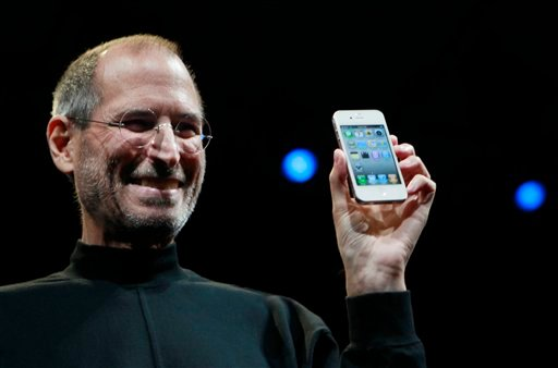 In this June 7, 2010, file photo, Apple CEO Steve Jobs smiles with a new iPhone at the Apple Worldwide Developers Conference in San Francisco. (AP)