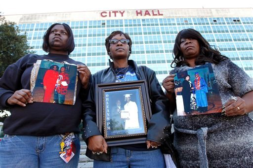 """In this Jan. 27, 2012 photo, members of the group """"Silence Is Violence,"""" an anti-crime group that includes surviving family members of murder victims, hold photos of their deceased loved ones at an event to memorialize New Orleanians who have been lost."""