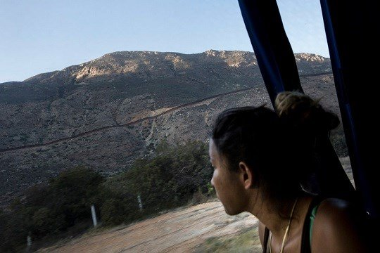 A Central American migrant looks out toward the border with the U.S., between Mexicali and Tijuana, as she rides by bus with a caravan of migrants to Tijuana, Mexico, Thursday, April 26, 2018. (AP Photo/Hans-Maximo Musielik)