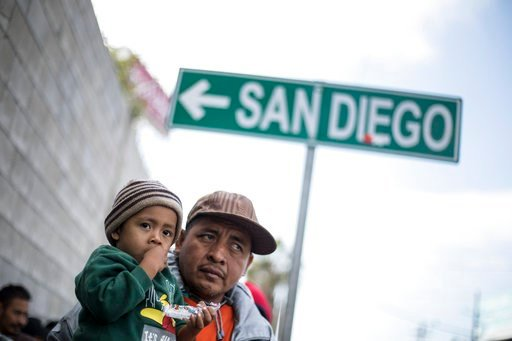 A father and his son await tutorship by immigration lawyers in Tijuana, Mexico, Friday, April 27, 2018. Close to to 200 migrants from Central America, mostly from Honduras, arrived in Tijuana seeking to enter the United States. (AP Photo/Hans-Maximo Musie