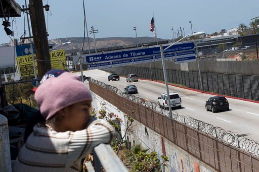 A migrant child from Honduras looks across the US-Mexico Border from Tijuana, Mexico, Friday, April 27, 2018. Close to 200 migrants from Central America, mostly from Honduras, arrived in Tijuana seeking to enter the United States. (AP Photo/Hans-Maximo Mu