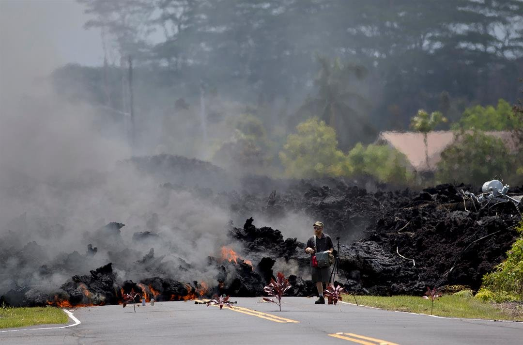 A man films the lava in the Leilani Estates subdivision, Saturday, May 5, 2018, in Pahoa, Hawaii. (AP Photo/Marco Garcia)