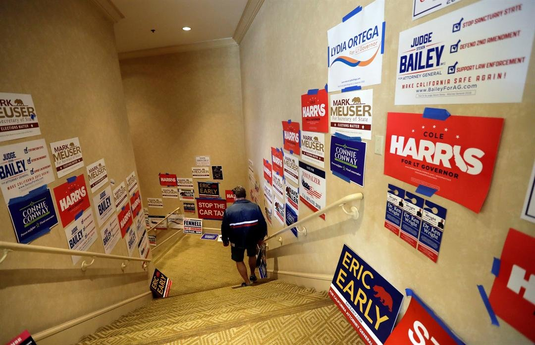 In this Saturday, May 5, 2018 photo, a man passes political posters during the California Republican Party convention in San Diego. (AP Photo/Gregory Bull)