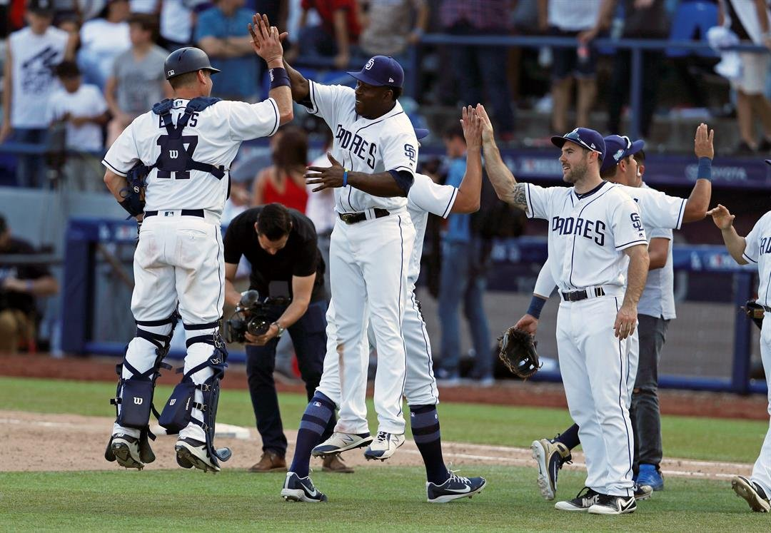 San Diego Padres catcher A.J. Ellis, left, celebrates with a Jose Pirela during final, ninth inning of a baseball game against Los Angeles Dodgers, Sunday, May 6, 2018, in Monterrey, Mexico. (AP Photo/Eduardo Verdugo)