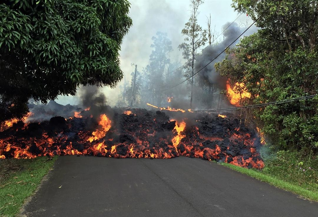 In this Sunday, May 6, 2018 photo provided by the U.S. Geological Survey, a lava flow moves across Makamae Street in the Leilani Estates subdivision near Pahoa on the island of Hawaii. U.S. Geological Survey via AP