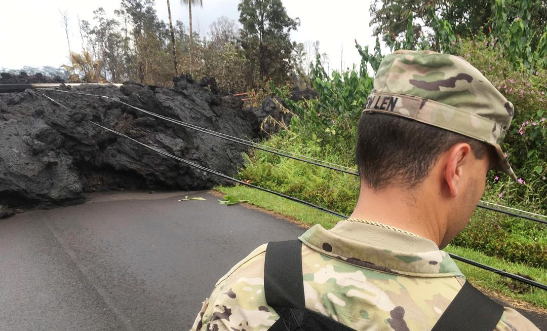 First Lt. Aaron Hew Len with the US National Guard surveys lava damage in the Leilani Estates subdivision near Pahoa, Hawaii, on Tuesday, May 8, 2018. (AP Photo/Caleb Jones)