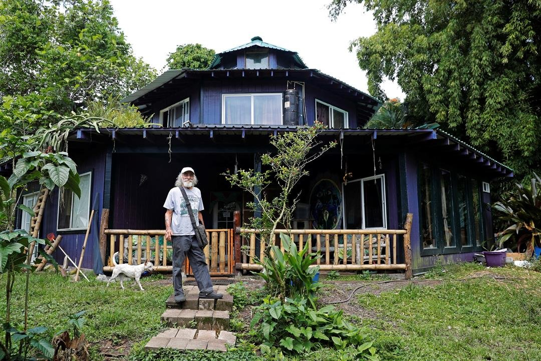 In this Saturday, May 5, 2018, photo, Edwin Montoya, 76, poses for a photo outside his home near Pahoa, Hawaii. (AP Photo/Marco Garcia)