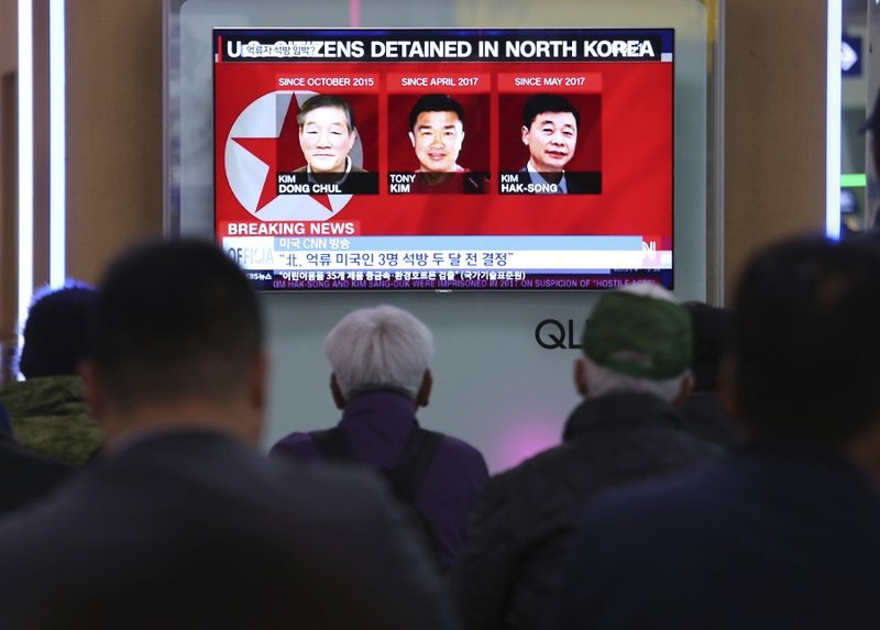 In this May 3, 2018 photo, people watch a TV news report screen showing portraits of three Americans, Kim Dong Chul, left, Tony Kim and Kim Hak Song, right, detained in the North Korea, at the Seoul Railway Station in Seoul, South Korea.