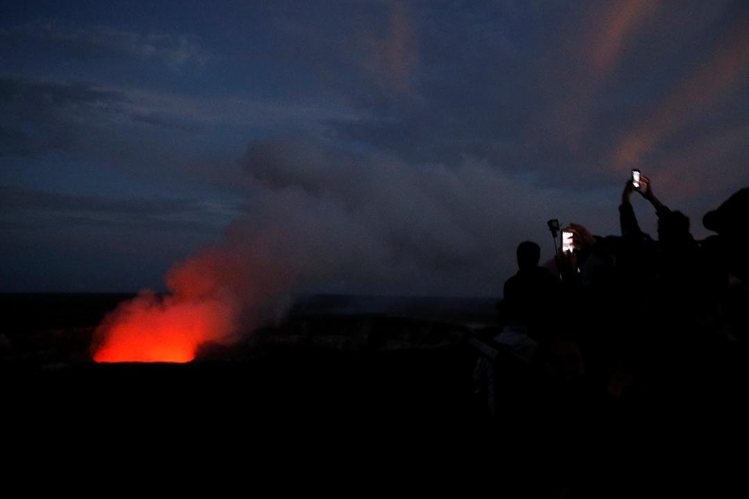 Visitors take pictures as Kilauea's summit crater glows red in Volcanoes National Park, Hawaii, Wednesday, May 9, 2018. (AP Photo/Jae C. Hong)