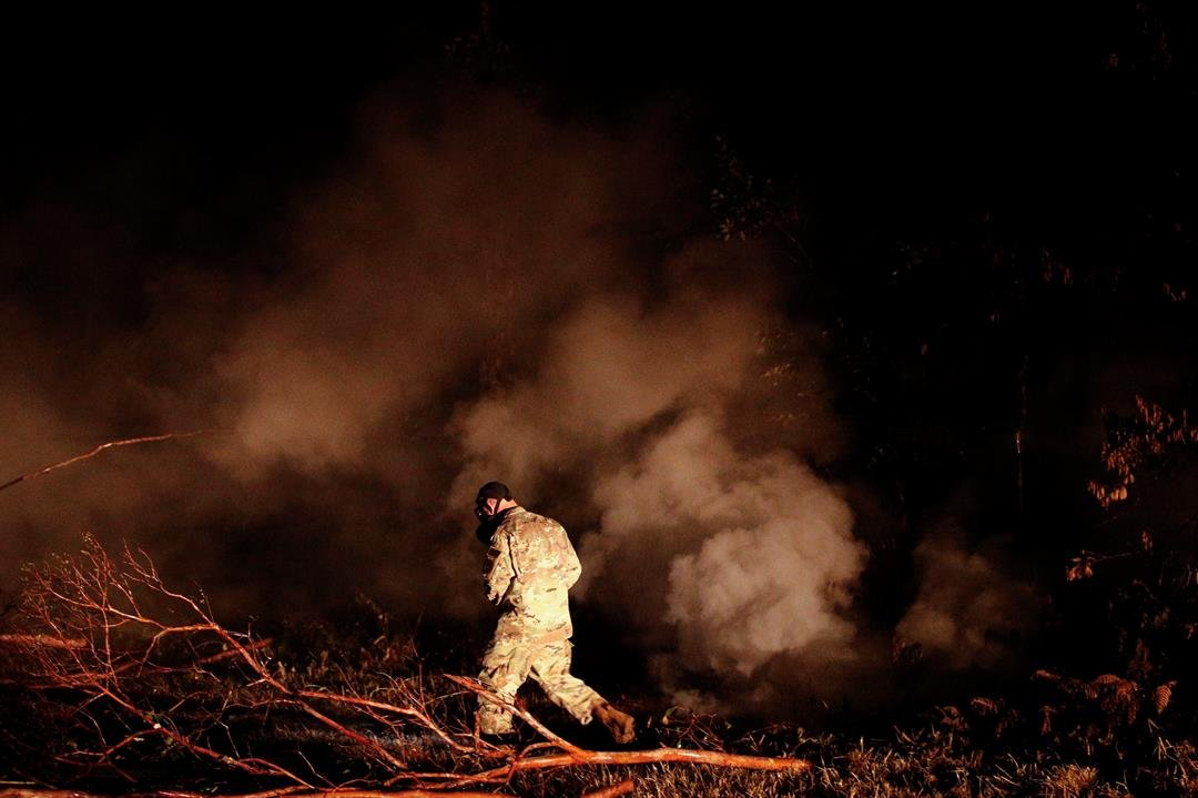 Sgt. 1st Class Carl Satterwaite, of the U.S. National Guard, tests air quality near cracks emitting volcanic gases from a lava flow in the Leilani Estates subdivision near Pahoa, Hawaii Thursday, May 10, 2018. (AP Photo/Jae C. Hong)