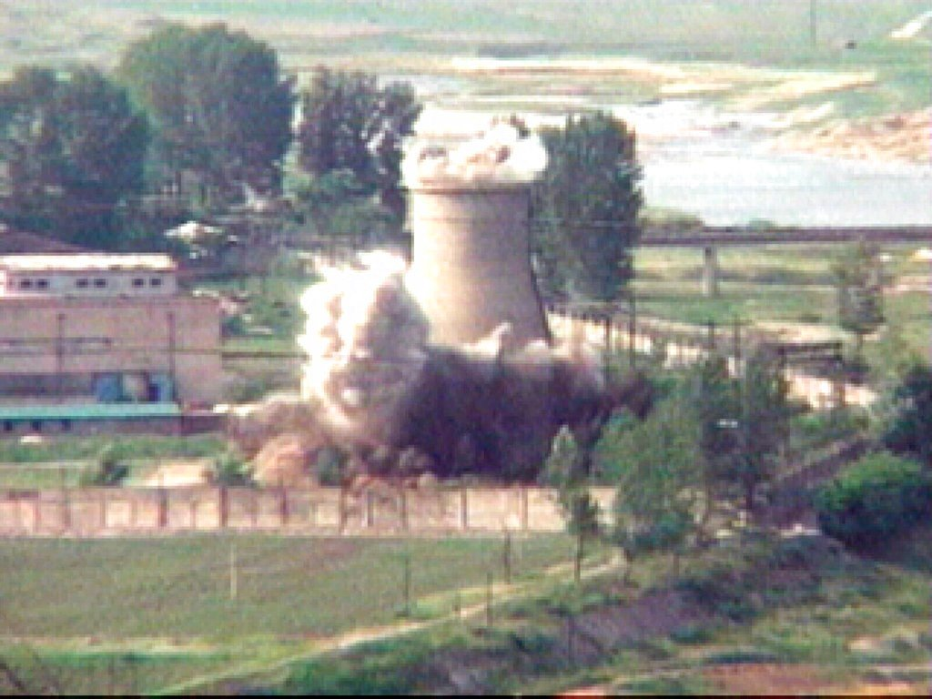 "In this file image from TV, the demolition of the 60-foot-tall cooling tower at its main reactor complex in Yongbyon North Korea. North Korea said it will hold a ""ceremony"" for the dismantling of its nuclear test site. (AP Photo/APTN, File)"