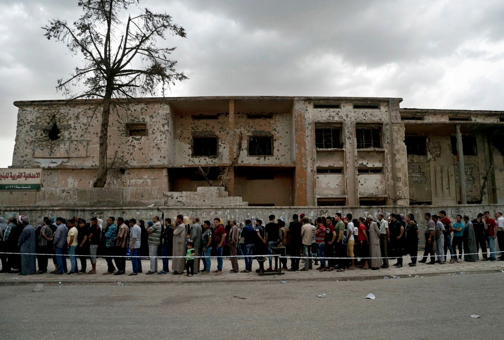 Iraqis wait in a long line to cast their vote in the country's election at a polling site in a battle-damaged building in west Mosul. This is the first parliamentary election since the Islamic State group was driven from the city.(AP Photo/Maya Alleruzzo)