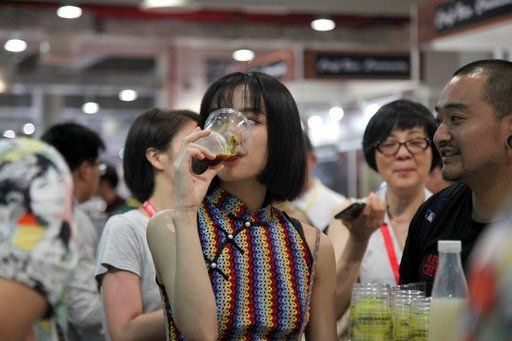 In this Thursday, May 17, 2018, photo, a woman drinks beer at the 2018 Craft Beer of China Exhibition in Shanghai. (AP Photo/Fu Ting)