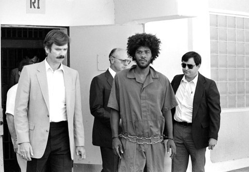 FILE - In this July 31, 1983, file photo, Kevin Cooper, center, a suspect in connection with the slashing death of four people in Chino, is escorted to a car for transport to San Bernadino from Santa Barbara, Calif.  (AP Photo/File)