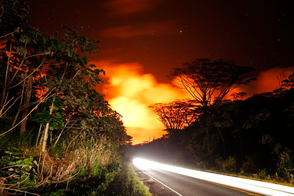As lava activity erupts in the background, cars drive down Hwy 132, Friday, May 18, 2018, near Pahoa, HI. (AP Photo/Marco Garcia)
