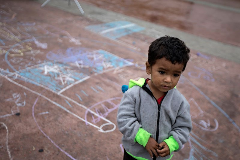 A child stands on a pavement adorned with chalk drawings at the El Chaparral U.S.-Mexico border crossing, in Tijuana, Mexico, Wednesday, May 2, 2018.