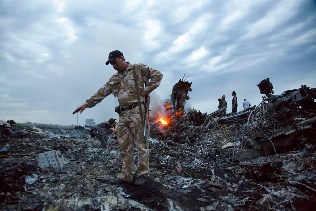 FILE - In this July 17, 2014. file photo, people walk amongst the debris at the crash site of a passenger plane near the village of Grabovo, Ukraine. (AP Photo/Dmitry Lovetsky, File)
