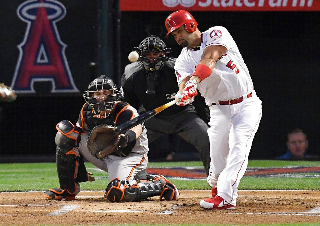 FILE - In this May 2, 2018, file photo, Los Angeles Angels' Albert Pujols, right, hits a solo home run in front of Baltimore Orioles catcher Caleb Joseph, left, and home plate umpire Roberto Ortiz. (AP Photo/Mark J. Terrill, File)