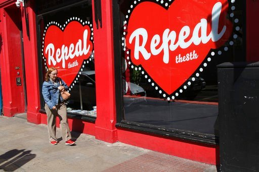 "In this May 17, 2018 photo, a woman walks past a ""Yes"" campaign logo on a shop window in Dublin, Ireland, ahead of the abortion referendum on Friday, May 25. (AP Photo/Peter Morrison)"