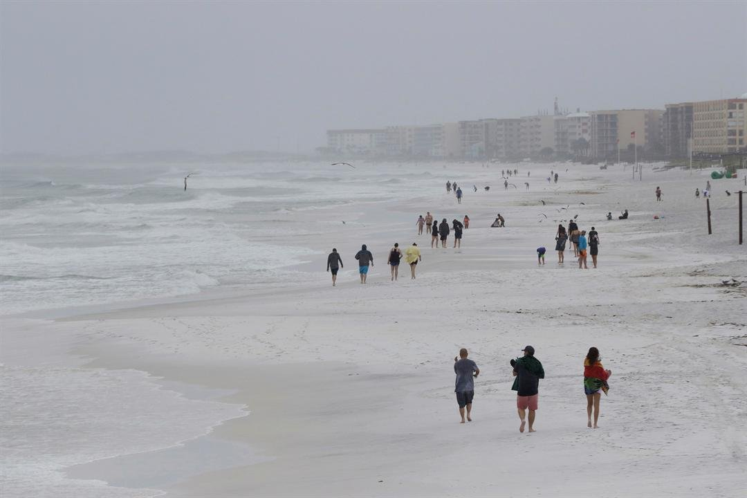 People walk the beach as a subtropical storm makes landfall on Monday, May 28, 2018 in Okaloosa Island, Fla. (AP Photo/Dan Anderson)