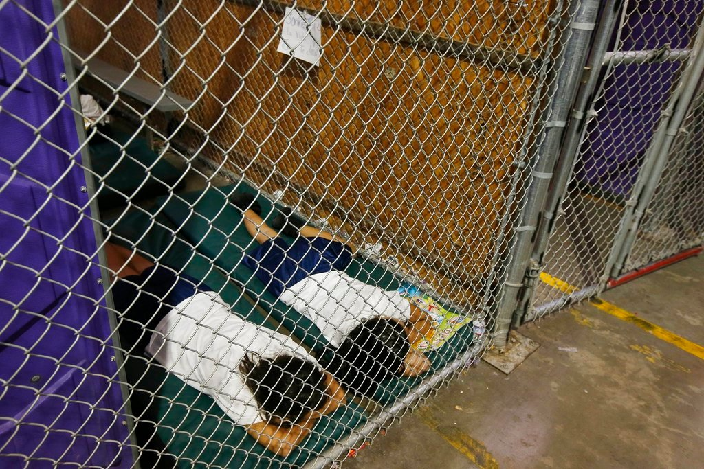 FILE - In this 2014 file photo, two detainees sleep in a holding cell, as the children are separated by age group and gender. (AP Photo/Ross D. Franklin, Pool)