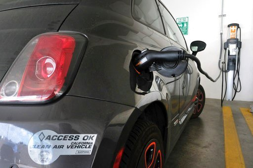 FILE - In this April 25, 2016, file photo, an electric Fiat plugged into a charging station in a parking lot in Los Angeles.  (AP Photo/Richard Vogel, File)
