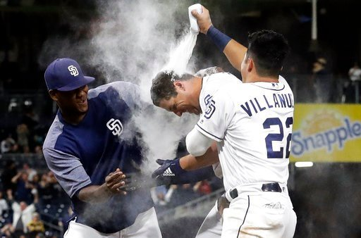 San Diego Padres third baseman Christian Villanueva (22) squeezes powder onto Hunter Renfroe, center, after Renfroe drove in the winning run against the Miami Marlins in a baseball game Wednesday, May 30, 2018, in San Diego. The Padres won 3-2. (AP Photo/