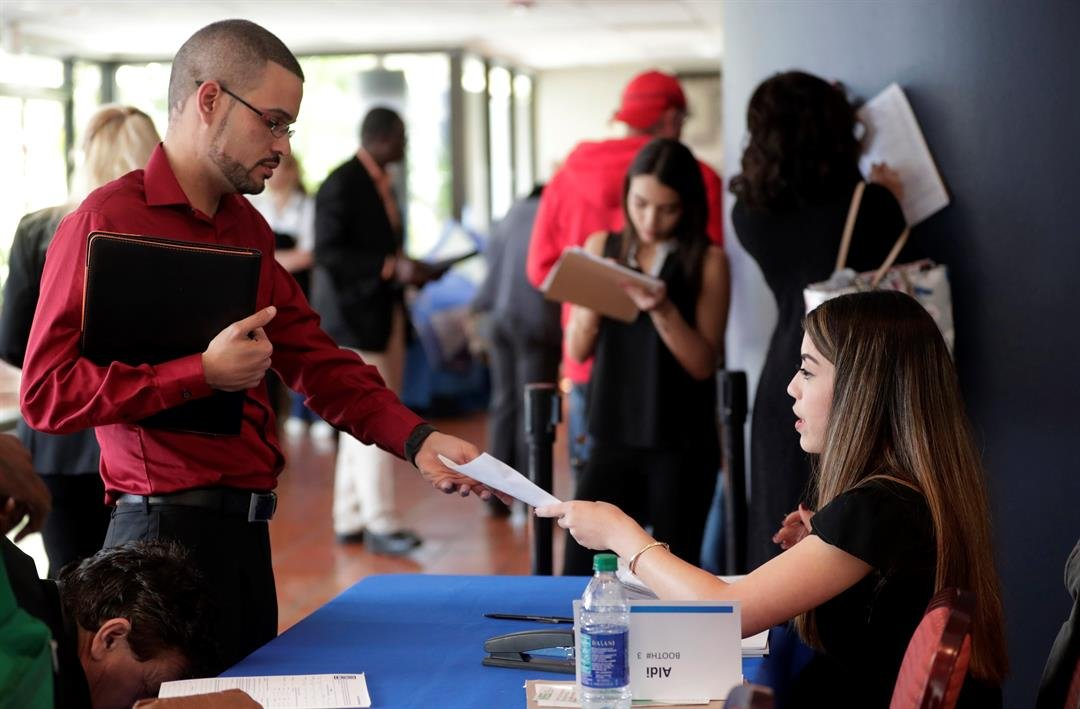 FILE- In this Jan. 30, 2018, file photo, an employee of Aldi, right, takes an application from a job applicant at a JobNewsUSA job fair in Miami Lakes, Fla. On Friday, April 6, the U.S. government issues the March jobs report.(AP Photo/Lynne Sladky, File)