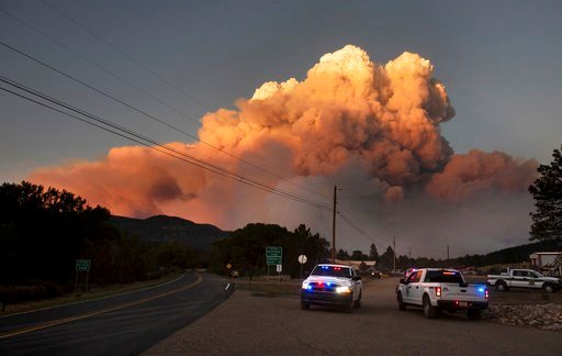 In this photo taken Thursday, May 31, 2018 and provided by Taosnews.com, officials confer as smoke rises from the Ute Park Fire in Ute Park, N.M. (Morgan Timms/Taosnews.com via AP)