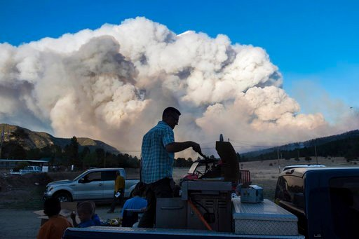 In this May 31, 2018 photo provided by Taosnews.com, faculty of Cimarron Municipal Schools cook hot dogs and chicken for first responders on the scene of the Ute Park Fire from the back of a pickup truck at the intersection of Hummingbird Lane and U.S. Hi