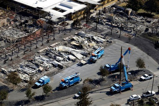 FILE - In this Oct. 14, 2017, file photo, PG&E crews work on restoring power lines in a fire ravaged neighborhood in an aerial view in the aftermath of a wildfire in Santa Rosa, Calif.(AP Photo/Marcio Jose Sanchez, File)