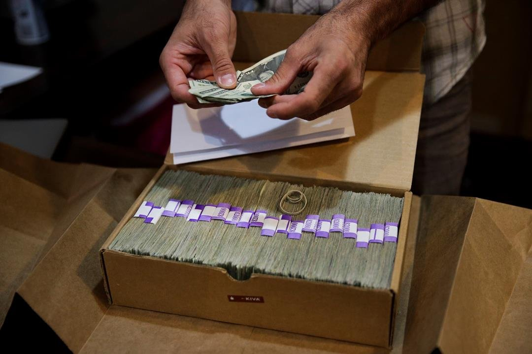 Jerred Kiloh, of the Higher Path medical marijuana dispensary, prepares his monthly tax payment, $40,131.88 in cash in Los Angeles. For Kiloh, the cash is a daily hassle. It needs to be counted repeatedly to safeguard against loss. (AP Photo/Jae C. Hong)