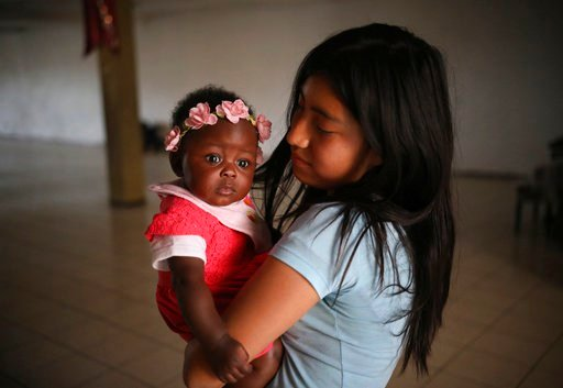 In this May 6, 2018 photo, a girl babysits a Mexican-born baby of Haitian descent at a church in Tijuana, Mexico.